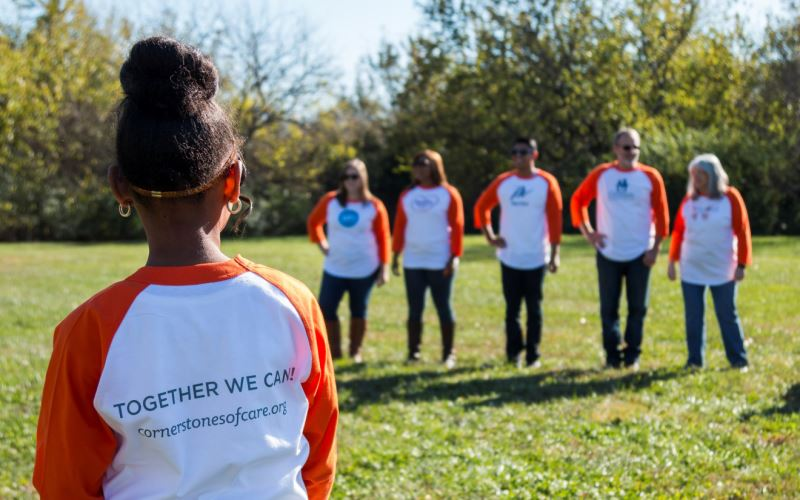 "Child wearing a Cornerstones of Care ""Together We Can"" shirt looking at adults in the distance."