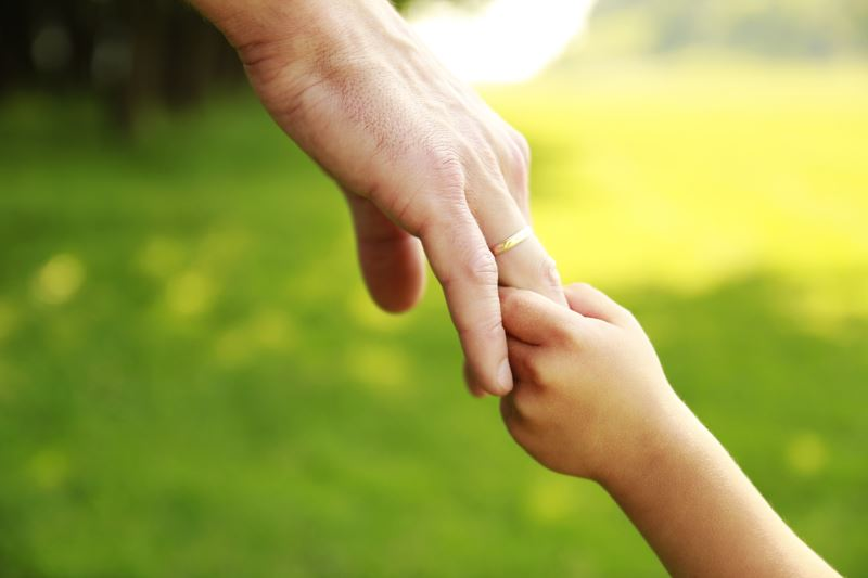Adult holding a child's hand to guide them.
