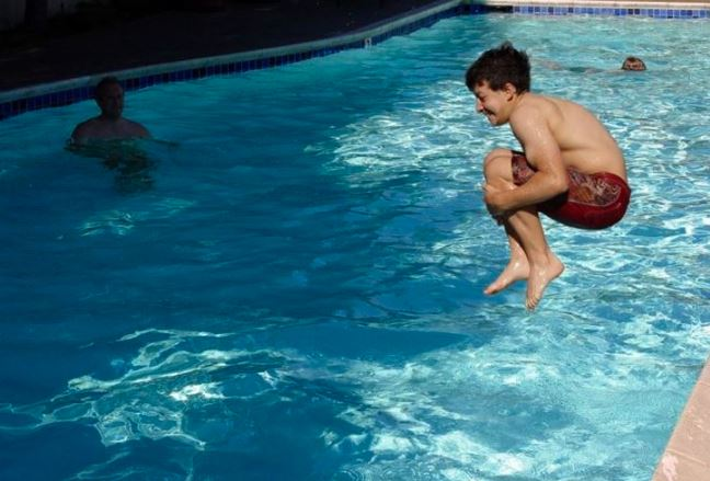 Boy jumping in swimming pool.